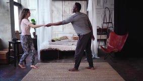Mujer joven que corre a través del cuarto y que salta en las manos del hombre Pares multiétnicos en abrazos y besos de los pijama almacen de metraje de vídeo