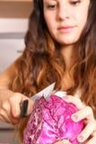 Mujer joven que corta la col roja Foto de archivo libre de regalías