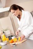 Mujer joven que corta la naranja en cocina Imagenes de archivo