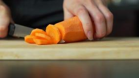 Mujer joven que corta la zanahoria almacen de video