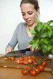 Mujer joven que corta los tomates frescos Fotografía de archivo libre de regalías