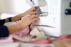 Mujer joven que cose mientras que se sienta en su lugar de trabajo Imagenes de archivo