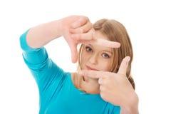 Mujer joven que crea el marco con los fingeres Fotos de archivo libres de regalías