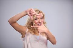 Mujer joven que crea un marco con los fingeres Foto de archivo