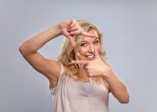 Mujer joven que crea un marco con los fingeres Imagenes de archivo