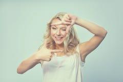 Mujer joven que crea un marco con los fingeres Fotos de archivo