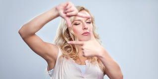 Mujer joven que crea un marco con los fingeres Imagen de archivo