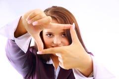 Mujer joven que crea un marco con sus dedos Fotografía de archivo libre de regalías