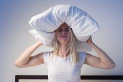Mujer joven que cubre los oídos con la almohada debido a ruido foto de archivo libre de regalías