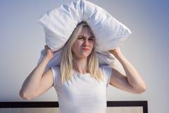 Mujer joven que cubre los oídos con la almohada debido a ruido fotografía de archivo