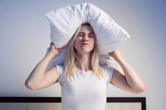 Mujer joven que cubre los oídos con la almohada debido a ruido imagen de archivo libre de regalías