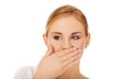 Mujer joven que cubre su boca con la mano Imagen de archivo libre de regalías