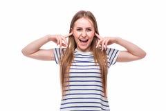 mujer joven que cubre sus oídos en el fondo blanco Fotografía de archivo libre de regalías