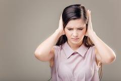 Mujer joven que cubre sus oídos No oiga ningún concepto malvado Foto de archivo