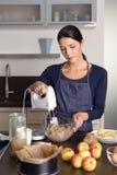 Mujer joven que cuece una empanada de manzana en la cocina Fotos de archivo libres de regalías
