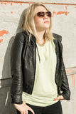 Mujer joven que cuelga hacia fuera y que goza del sol contra una pared Imágenes de archivo libres de regalías