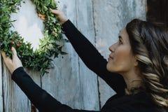Mujer joven que cuelga una guirnalda de la Navidad en su hogar Foto de archivo libre de regalías