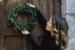 Mujer joven que cuelga una guirnalda de la Navidad en su hogar Fotos de archivo libres de regalías