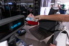 Mujer joven que da el dinero al cajero en la tienda de la moda foto de archivo