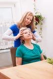 Mujer joven que da masajes al cuero cabelludo femenino de los mayores Fotografía de archivo