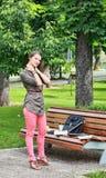 Mujer joven que da masajes a su nuca en un parque Fotos de archivo libres de regalías