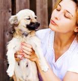 Mujer joven que da un beso a su perro divertido imagenes de archivo
