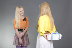 Mujer joven que da un presente a su amigo sobre gris Imágenes de archivo libres de regalías
