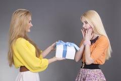 Mujer joven que da un presente a su amigo sorprendido Imágenes de archivo libres de regalías
