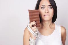 Mujer joven que decide sosteniendo el chocolate y la cinta de la medida imágenes de archivo libres de regalías