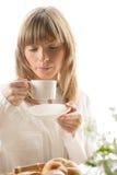 Mujer joven que desayuna Imagen de archivo