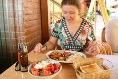 Mujer joven que desayuna Fotos de archivo