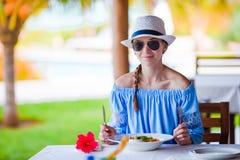 Mujer joven que desayuna en el café al aire libre el vacaciones de verano Foto de archivo