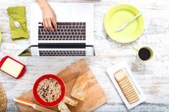Mujer joven que desayuna mientras que usa un ordenador portátil imagen de archivo