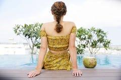 Mujer joven que descansa por la piscina fotografía de archivo libre de regalías