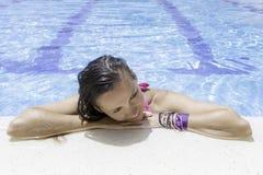 Mujer joven que descansa sobre el borde de la piscina fotos de archivo