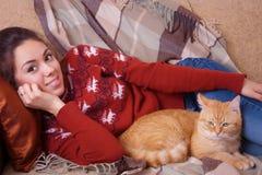 Mujer joven que descansa sobre el sofá con un gato Foto de archivo