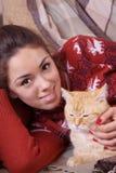 Mujer joven que descansa sobre el sofá con un gato Imagenes de archivo