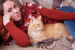 Mujer joven que descansa sobre el sofá con un gato Imágenes de archivo libres de regalías