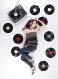 Mujer joven que descansa sobre la música que escucha del piso Fotos de archivo