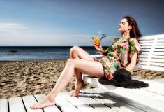 Mujer joven que descansa sobre la playa imagenes de archivo