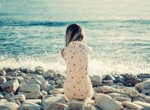 Mujer joven que descansa sobre Pebble Beach Imagenes de archivo