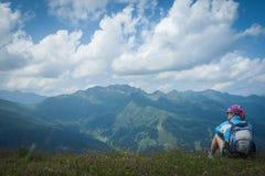 Mujer joven que descansa sobre un alza de la montaña fotografía de archivo