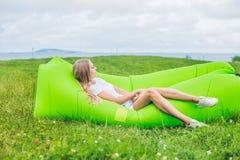 Mujer joven que descansa sobre un sofá del aire en el parque Fotografía de archivo libre de regalías