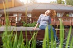 Mujer joven que descansa y que se divierte en el parque que se sienta en un embarcadero sobre el lago Fotografía de archivo