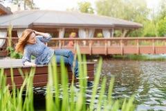Mujer joven que descansa y que se divierte en el parque que se sienta en un embarcadero sobre el lago Imagen de archivo
