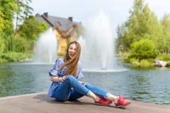Mujer joven que descansa y que se divierte en el parque que se sienta en un embarcadero sobre el lago Fotografía de archivo libre de regalías