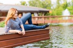 Mujer joven que descansa y que se divierte en el parque que se sienta en un embarcadero sobre el lago Imágenes de archivo libres de regalías