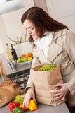 Mujer joven que desempaqueta el bolso de compras en cocina Imagen de archivo