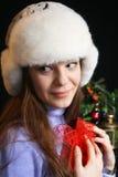 Mujer joven que desempaqueta el regalo de la Navidad imagen de archivo
