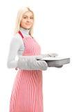 Mujer joven que desgasta cocinando las manoplas y el delantal   Imagen de archivo